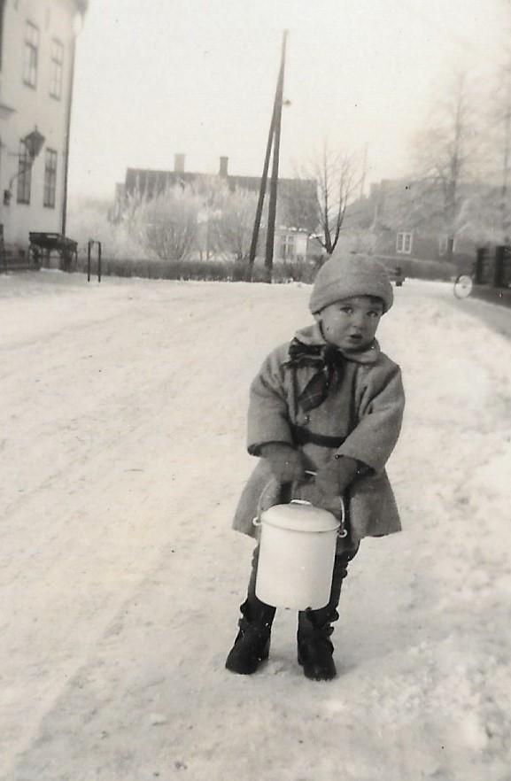 Den unge mannen med mjölkspannen är Bengt, fotograferad 1931 med den gamla klockarbostaden i bakgrunden.